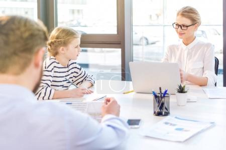 businesswoman and businessman with daughter in office