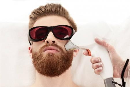 man receiving laser skin care