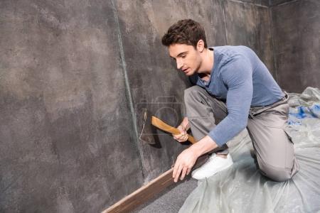 Young laborer repairing floor
