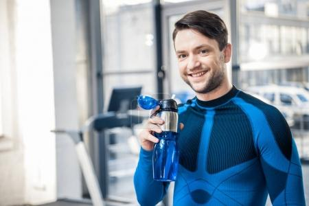 Man with bottle of water at gym