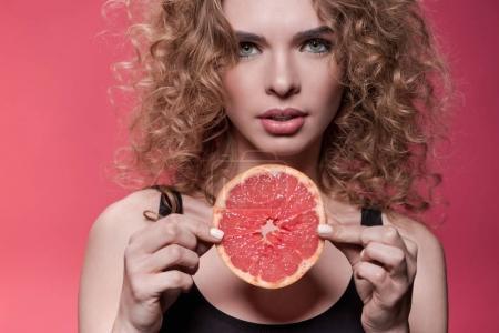 Woman holding piece of grapefruit