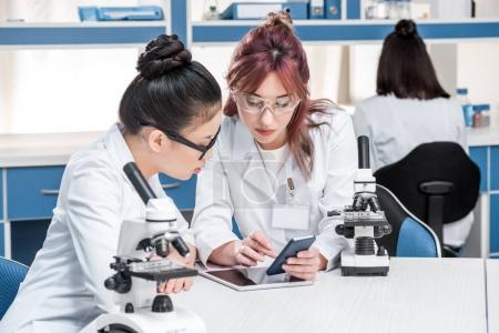 Scientists working together with microscopes