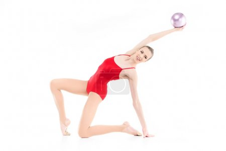 Rhythmic gymnast exercising with ball