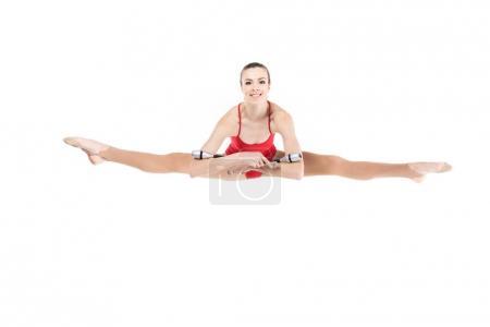 Woman rhythmic gymnast jumping with clubs