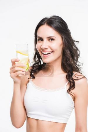 Woman holding glass of water with lemon