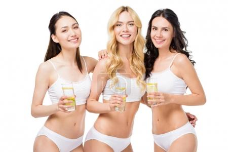 Women holding glasses of water with lemon