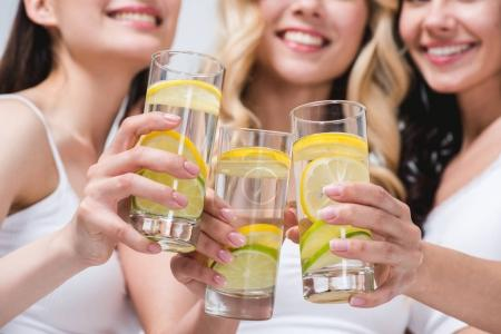 Women clinking with glasses of water with lemon