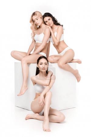 Sensual women posing while sitting on box