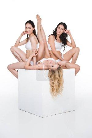 Women in white underwear lying on box