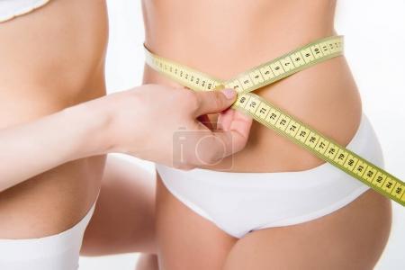 Girls using measuring tape to waist