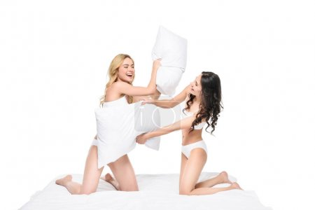 Young women playing pillow fight