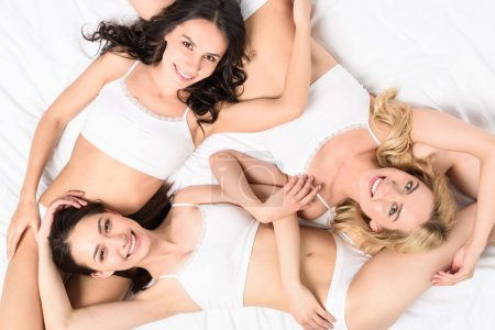 Women in white underwear lying on bed