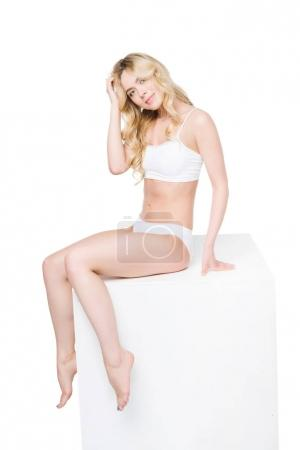 Young woman in white underwear sitting