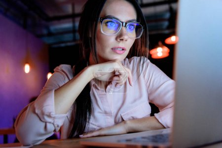 Caucasian businesswoman in glasses looking at laptop