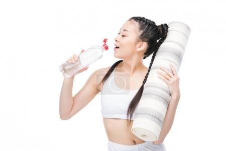 Girl with yoga mat drinking water
