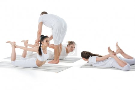 Girls doing Frog Pose with instructor