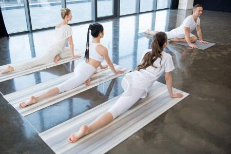 Women doing yoga position with instructor