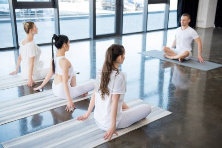 Women sitting in lotus pose with instructor