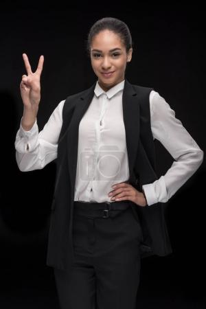 Businesswoman gesturing victory sign