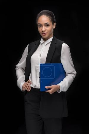 Young businesswoman standing with clipboard
