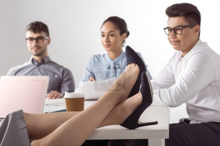 Businesswoman sitting with legs on table