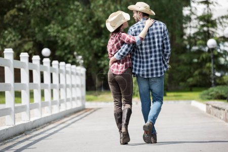 Cowboy with girlfriend walking on pathway in park