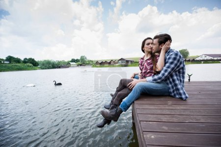 Young couple sitting on wooden pier