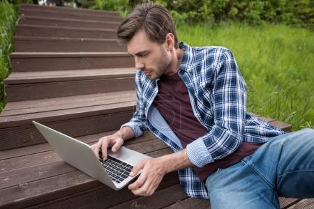 Casual man using laptop at park