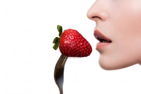 Young woman eating strawberry on fork