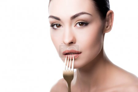 Young woman pressing fork to lips