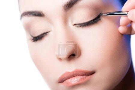 Makeup artist applying eyeliner arrows