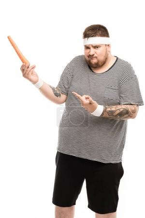 Fat man pointing with finger at carrot