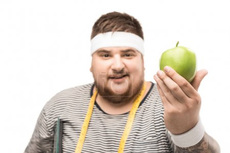 Young chubby man holding apple