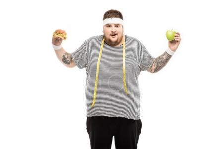 Fat man holding burger and apple