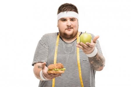 Chubby man holding burger and apple