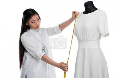 Fashion designer measuring dress on dummy