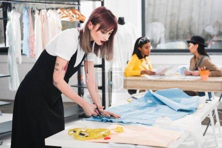Dressmaker cutting blue fabric with scissors