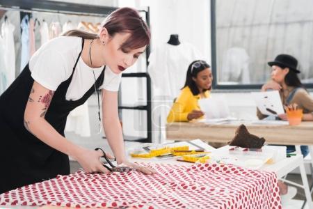 Dressmaker cutting fabric with scissors