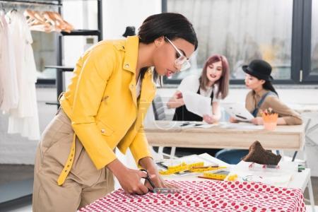 African american dressmaker cutting fabric