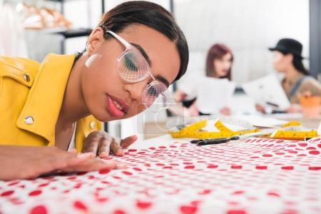 African american dressmaker fitting fabric