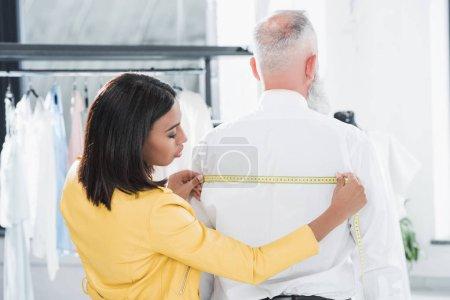 Tailor measuring elderly man