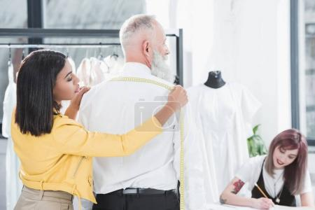 Tailor measuring grey haired man