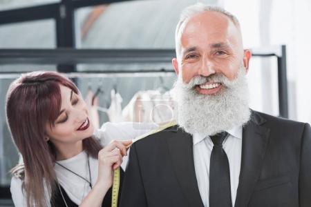 Tailor fitting smiling elderly man