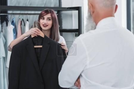Tailor proposing man to try on jacket