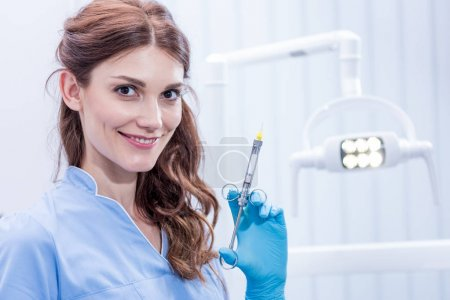 Dentist with dental syringe