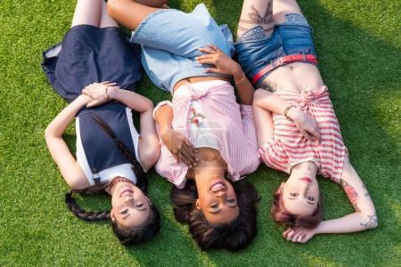 Multiethnic girls lying on grass