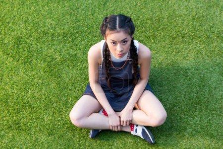 Asian girl sitting on grass