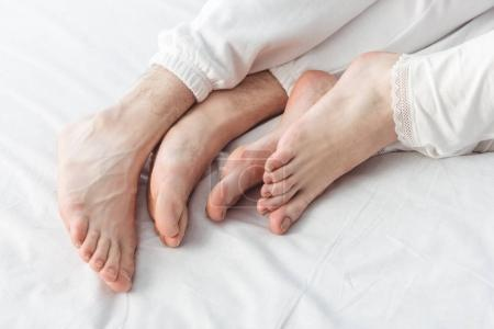 Feet of couple lying in bed