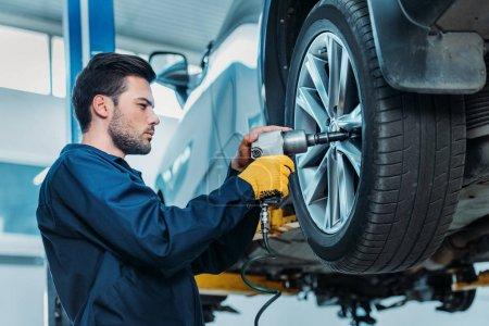 Automechanic unscrewing tire bolts