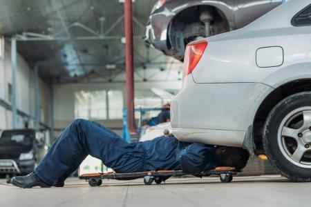 Automechanic lying on creeper
